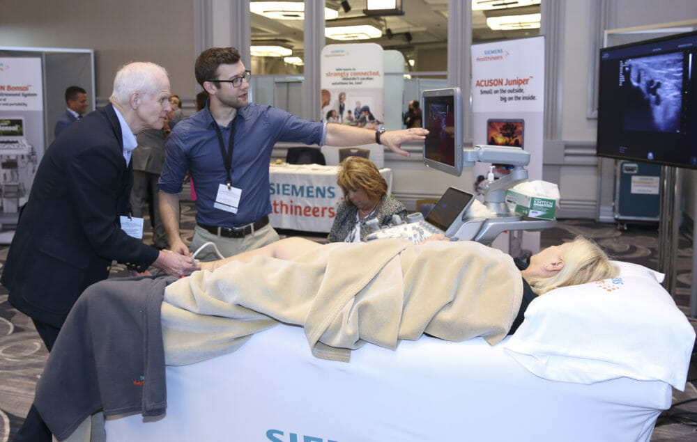 Healthcare and Medical Photography of male conference attendee practcing on live patient | proimagesphoto.com