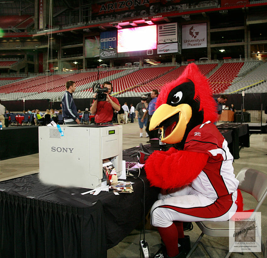 Photo of the Arizona Cardinal Mascot working the proimagesphoto.com onsite printing and social media station
