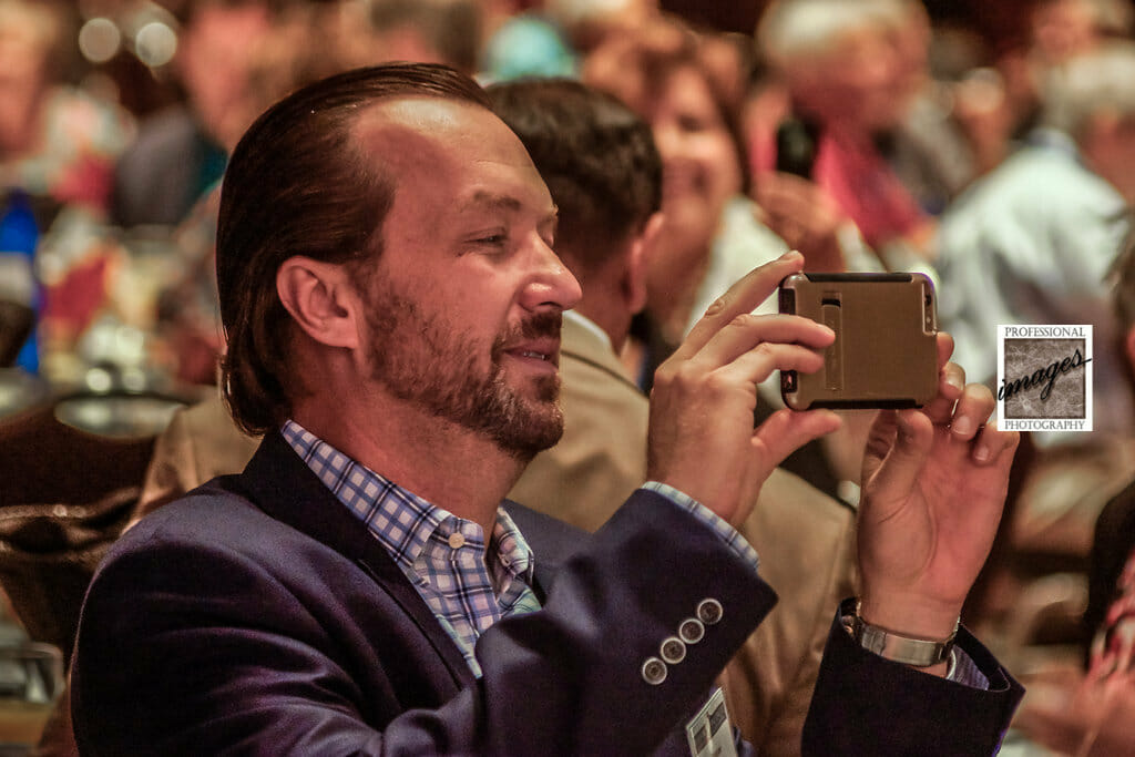 Houston Convention photography of Attendee in audience using phone to videotape speaker