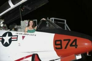 Female sitting in a Navy Jet on the USS Midway for a photo printed onsite by proimagesphoto