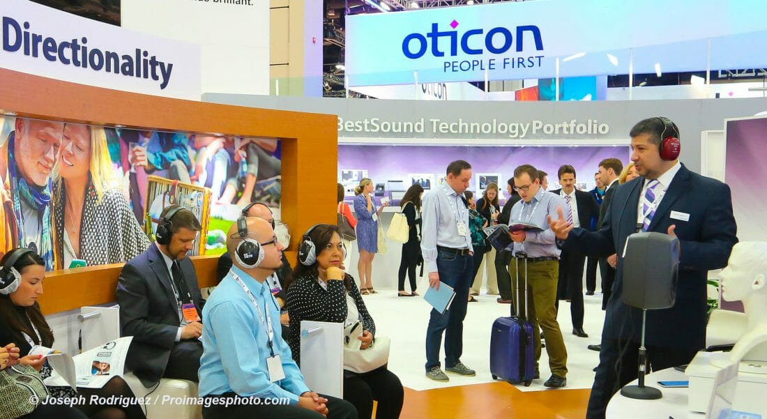 Tradeshow Photography of attendees listening to presenter in Tradeshow Booth.