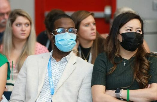 Convention Photography of Convention Attendees, some wearing masks and other no mask during a breakout session.