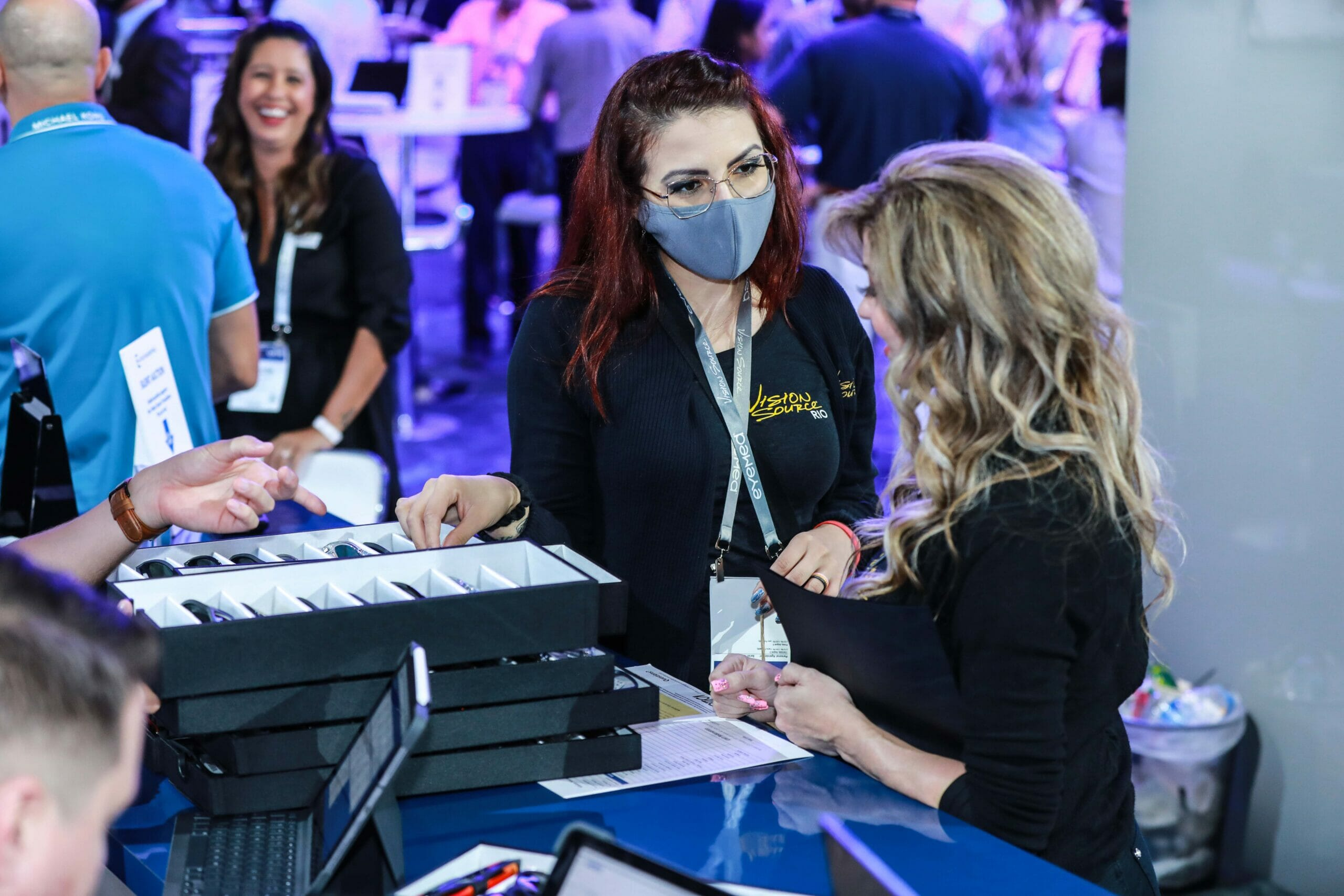 Convention, Event and Tradeshow Photography of female Exhibitor showing attendee product.